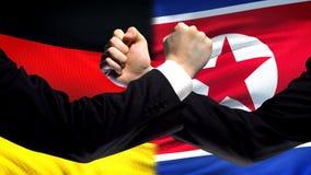 La Germania contro confronto della Corea del Nord, pugni sul fondo della bandiera, diplomazia immagini stock libere da diritti