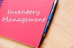 La gestión de inventario escribe en el cuaderno foto de archivo