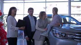 La gestione commerciale automatica, giovane famiglia dei compratori con la ragazza del bambino comunica con il responsabile dell'