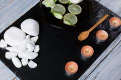 La ghiaia bianca, aroma delle candele, un cucchiaio di legno e una ciotola profonda di acqua, di limone e di germogli dei fiori fotografia stock