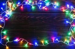 La ghirlanda brillante rasenta il fondo di legno Fotografia Stock