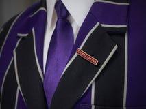 La giacca sportiva dei ragazzi di scuola con gli sport capitana il distintivo di scuola Fotografia Stock Libera da Diritti
