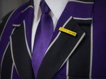 La giacca sportiva dei ragazzi di scuola con gli sport capitana il distintivo di scuola Fotografia Stock