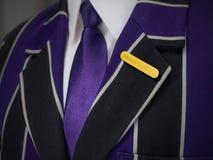 La giacca sportiva dei ragazzi di scuola con le bevande controlla il distintivo di scuola Fotografia Stock