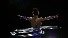 La ginnasta accende il corpo molti cerchi Priorità bassa nera Movimento lento video d archivio