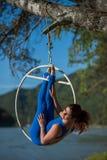 La ginnasta dai capelli rossi in un vestito blu che fa gli esercizi difficili all'aria suona in natura Fotografie Stock
