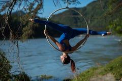 La ginnasta dai capelli rossi in un vestito blu che fa gli esercizi difficili all'aria suona in natura Fotografia Stock