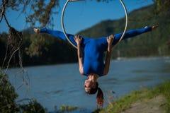La ginnasta dai capelli rossi in un vestito blu che fa gli esercizi difficili all'aria suona in natura Immagini Stock Libere da Diritti