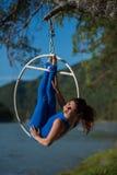 La ginnasta dai capelli rossi in un vestito blu che fa gli esercizi difficili all'aria suona in natura Fotografia Stock Libera da Diritti
