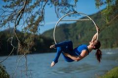 La ginnasta dai capelli rossi in un vestito blu che fa gli esercizi difficili all'aria suona in natura Immagini Stock