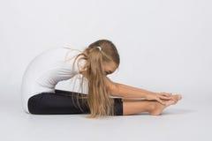 La ginnasta della ragazza esegue una pieghettatura che si siede sulle mani di tirate del pavimento alle dita del piede Fotografia Stock Libera da Diritti