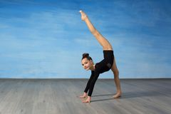 La ginnasta della ragazza sorride e mostra un esercizio relativo alla ginnastica sul pavimento su un fondo blu Le mani ? sul pavi immagini stock