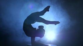 La ginnasta esegue i trucchi sulla tavola nello studio Fumi la priorità bassa Movimento lento Siluetta video d archivio