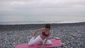 La ginnasta femminile sta allungando le mani e le gambe sulla spiaggia del mare del ciottolo di giorno video d archivio