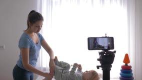 La ginnastica del bambino, giovane madre di blogger fa il riscaldamento a poco figlio e le annotazioni vivono il video d'istruzio stock footage