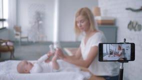 La ginnastica del bambino, madre di blogger fa gli esercizi per poca figlia e le annotazioni vivono il video d'istruzione sul cel video d archivio