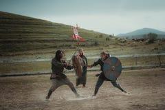 La giostra medievale knights la battaglia della posta sulle spade con gli schermi Immagini Stock Libere da Diritti