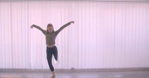 La giovane ballerina professionista caucasica tenera viene fuori dalla finestra comincia ballare charmingly in studio leggero stock footage