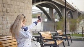 La giovane bella bionda fa il selfie facendo uso di uno smartphone Una giovane donna gode di una passeggiata lungo l'argine del f video d archivio