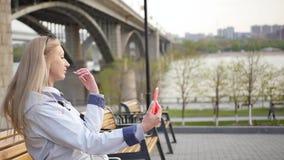 La giovane bella bionda fa il selfie facendo uso di uno smartphone Una giovane donna gode di una passeggiata lungo l'argine del f archivi video