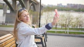 La giovane bella bionda fa il selfie facendo uso di uno smartphone Una giovane donna gode di una passeggiata lungo l'argine del f stock footage