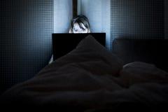 La giovane bella bugia sorridente della donna a letto si tiene per mano sul computer portatile Immagini Stock Libere da Diritti