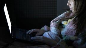 La giovane bella bugia sorridente della donna a letto si tiene per mano sul computer portatile Fotografia Stock