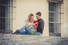 La giovane bella coppia nell'amore che celebra il giorno di biglietti di S. Valentino presenta e pane tostato Fotografie Stock Libere da Diritti