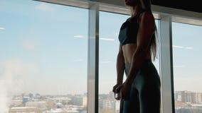La giovane bella donna è stante e facente l'allenamento tozzo con forte energia video d archivio