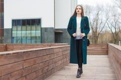 La giovane bella donna alla moda che cammina giù la via in cappotto verde smeraldo e nel bianco ha tricottato il maglione fotografia stock libera da diritti