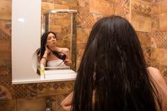 La giovane, bella donna asciuga i capelli nel bagno con un asciugacapelli fotografia stock libera da diritti
