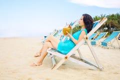 La giovane bella donna asiatica sta bevendo il succo della noce di cocco sulla spiaggia Immagini Stock