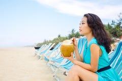 La giovane bella donna asiatica sta bevendo il succo della noce di cocco sulla spiaggia Fotografia Stock Libera da Diritti