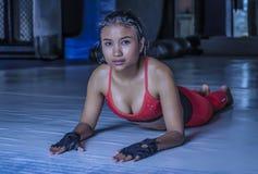La giovane bella donna asiatica sudata nello sport copre l'allungamento sulla posa sorridente del pavimento del dojo della palest Immagini Stock