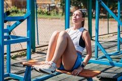 La giovane bella donna atletica scuote la stampa sul campo sportivo fotografie stock libere da diritti