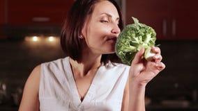La giovane bella donna attraente sta preparando cucinare qualcosa con i broccoli archivi video