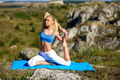 La giovane bella donna bionda che fa l'yoga si esercita su una roccia Fotografia Stock Libera da Diritti