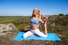 La giovane bella donna bionda che fa l'yoga si esercita su una roccia Immagini Stock