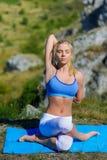 La giovane bella donna bionda che fa l'yoga si esercita su una roccia Fotografia Stock