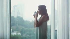 La giovane bella donna castana apre le tende che beve il caffè dalla finestra nella sua casa accogliente e considera la vista del archivi video