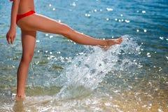 La giovane bella donna che cammina sulla spiaggia e spruzza l'acqua vicino immagine stock libera da diritti