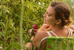 La giovane bella donna che si diverte il fiuto fiorisce la seduta su una sedia nel giardino un giorno di estate fotografia stock libera da diritti
