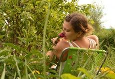 La giovane bella donna che si diverte il fiuto fiorisce la seduta su una sedia nel giardino un giorno di estate immagini stock