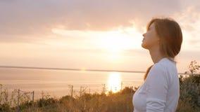 La giovane bella donna che si gira verso Dio in natura, pregare della ragazza ha piegato le sue mani al mento, concetto della rel archivi video
