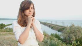 La giovane bella donna che si gira verso Dio in natura, pregare della ragazza ha piegato le sue mani al mento, concetto della rel video d archivio