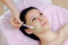 La giovane bella donna con capelli scuri ottiene la procedura nel salone di bellezza Immagine Stock Libera da Diritti