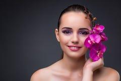 La giovane bella donna con il fiore dell'orchidea fotografie stock libere da diritti