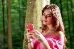 La giovane bella donna con il sorriso a trentadue denti invia il messaggio Fotografie Stock Libere da Diritti