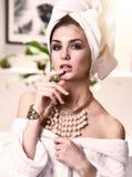 La giovane bella donna con l'asciugamano bianco sulla testa che esamina l'accappatoio d'uso dello specchio e l'oro imperlano i gi Immagine Stock