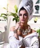 La giovane bella donna con l'asciugamano bianco sulla testa che esamina l'accappatoio d'uso dello specchio e l'oro imperlano i gi Immagini Stock